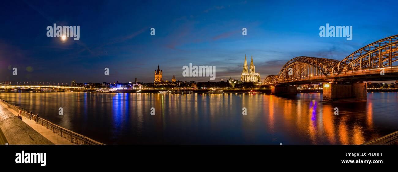 Breites Panorama von Köln, Deutschland mit Kathedrale und Brücke nach Sonnenuntergang an der blauen Stunde Panorama mit Rhein im Vordergrund. Stockbild