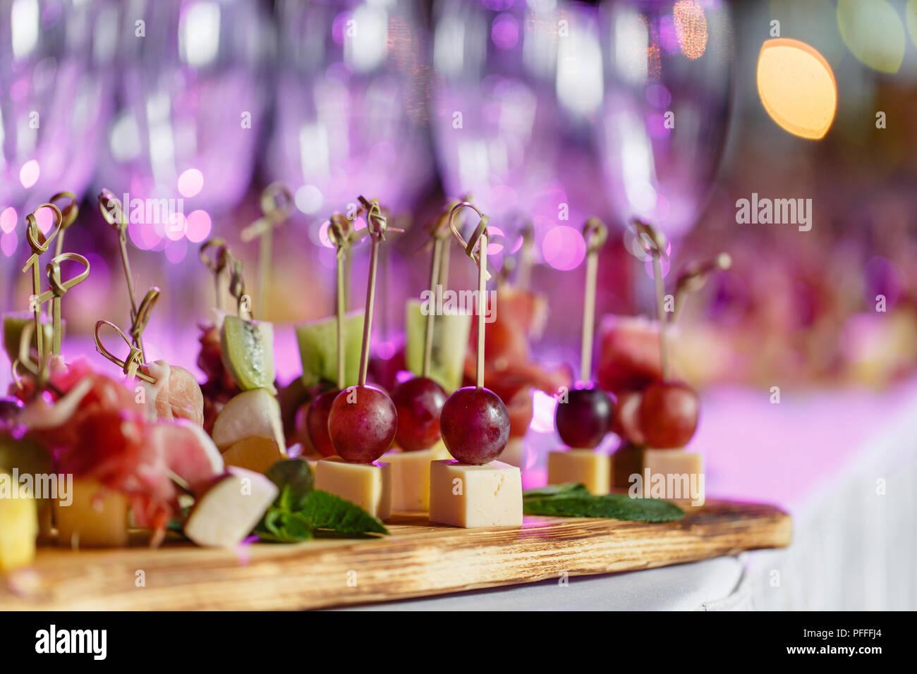Feierlichen Rutsch ins neue Jahr und Veranstaltungsräume. Viele Gläser Champagner oder Wein auf dem Tisch im Restaurant Buffet mit vielen leckeren Snacks. Canapees, Bruschetta, und kleine Desserts auf Holzplatte board Stockbild