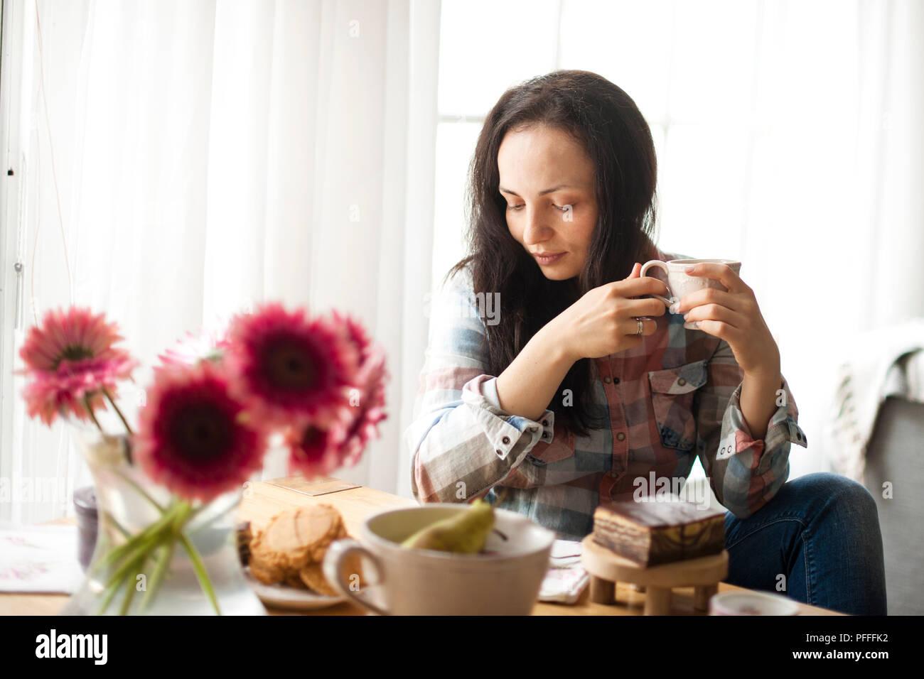 Frau mit einer Tasse Kaffee, einem guten Morgen zu Hause. Frühstück und duftenden Kaffee. Die Einrichtung ist gemütlich und die Blumen. Freier Platz für Text. Stockbild
