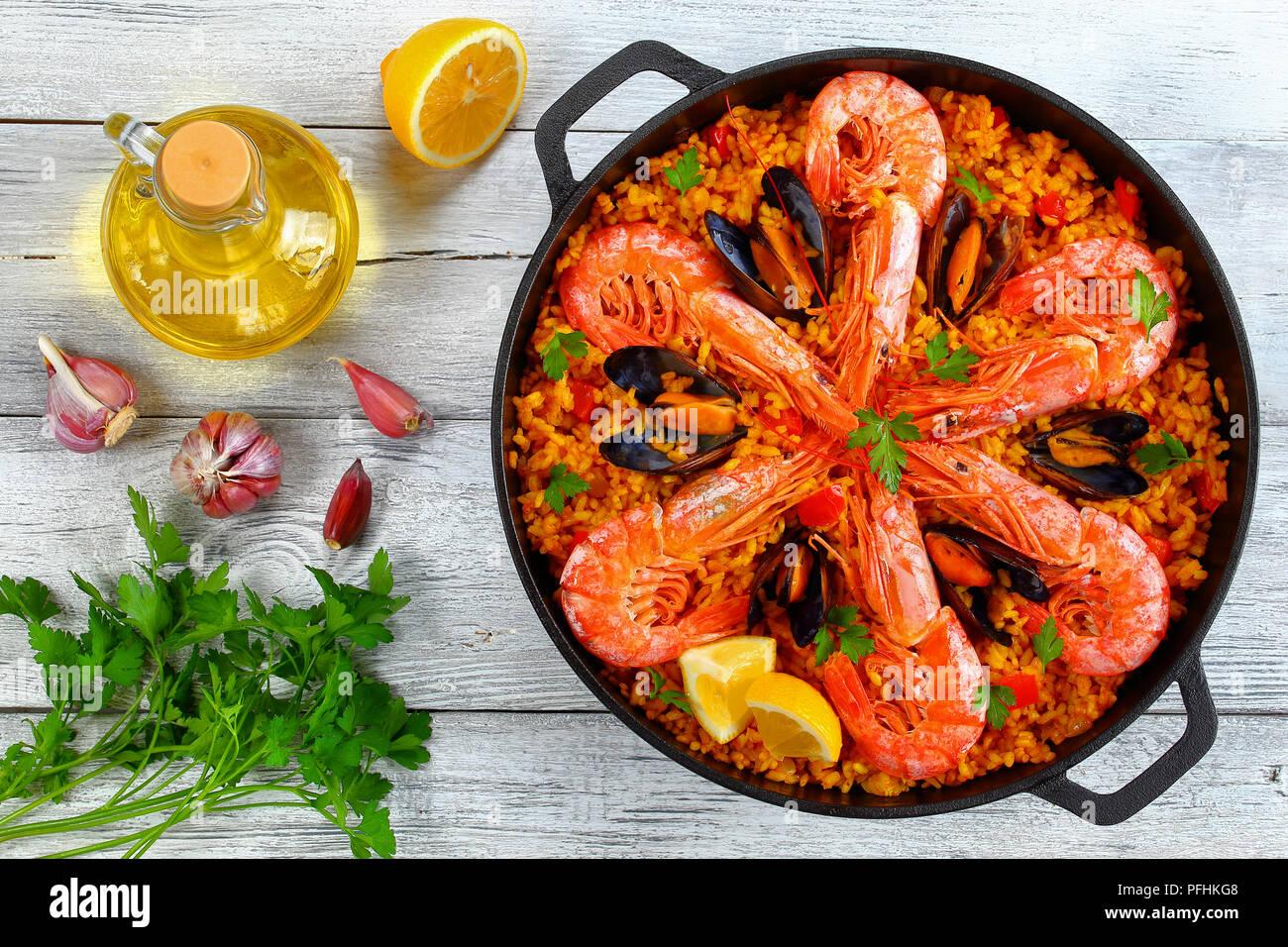 Köstliche Meeresfrüchte Valencia Paella mit Gambas, Muscheln auf herzhafte cremige Safran Reis mit Gewürzen und Zitrone Keile in der Wanne, auf alten Holztisch wit Stockfoto