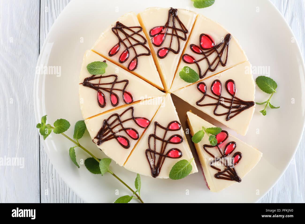In der Nähe von köstlichen kunstvoll mit Schokolade verziert und Gelee Käsekuchen mit frischen grünen Minze auf weißen platter auf Holztisch, horizontale Ansicht f Stockbild