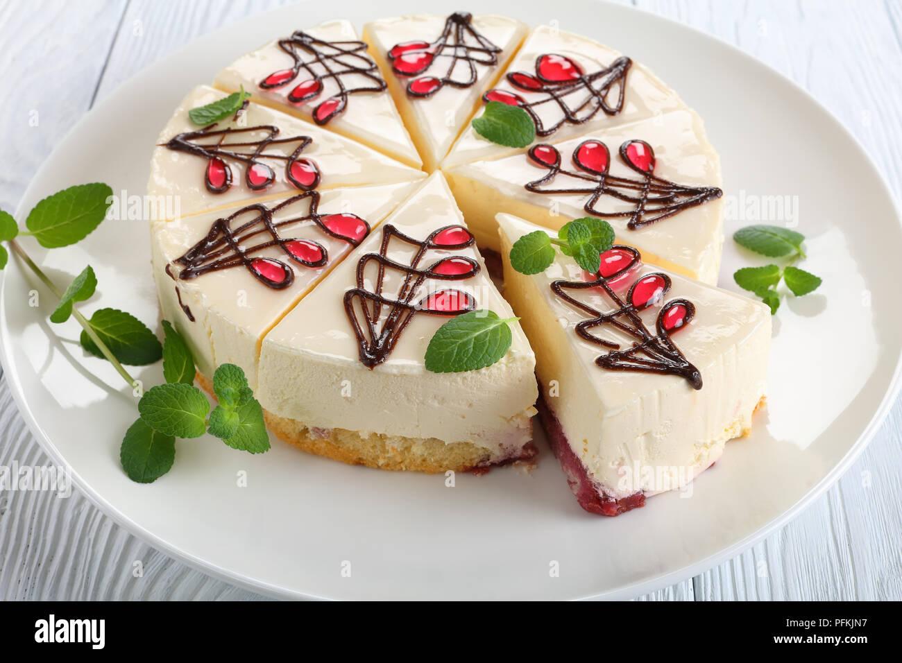Nahaufnahme der kunstvoll mit Schokolade verziert und Gelee Käsekuchen mit untere Schicht besteht aus biskuitteig mit Berry Soße, auf weissem platter auf Woo Stockbild