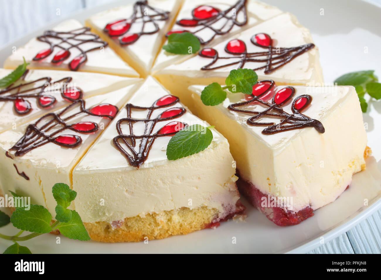 Nahaufnahme der Käsekuchen mit untere Schicht besteht aus biskuitteig mit Berry Soße, auf weissem platter auf Holztisch, horizontale Ansicht von oben Stockbild