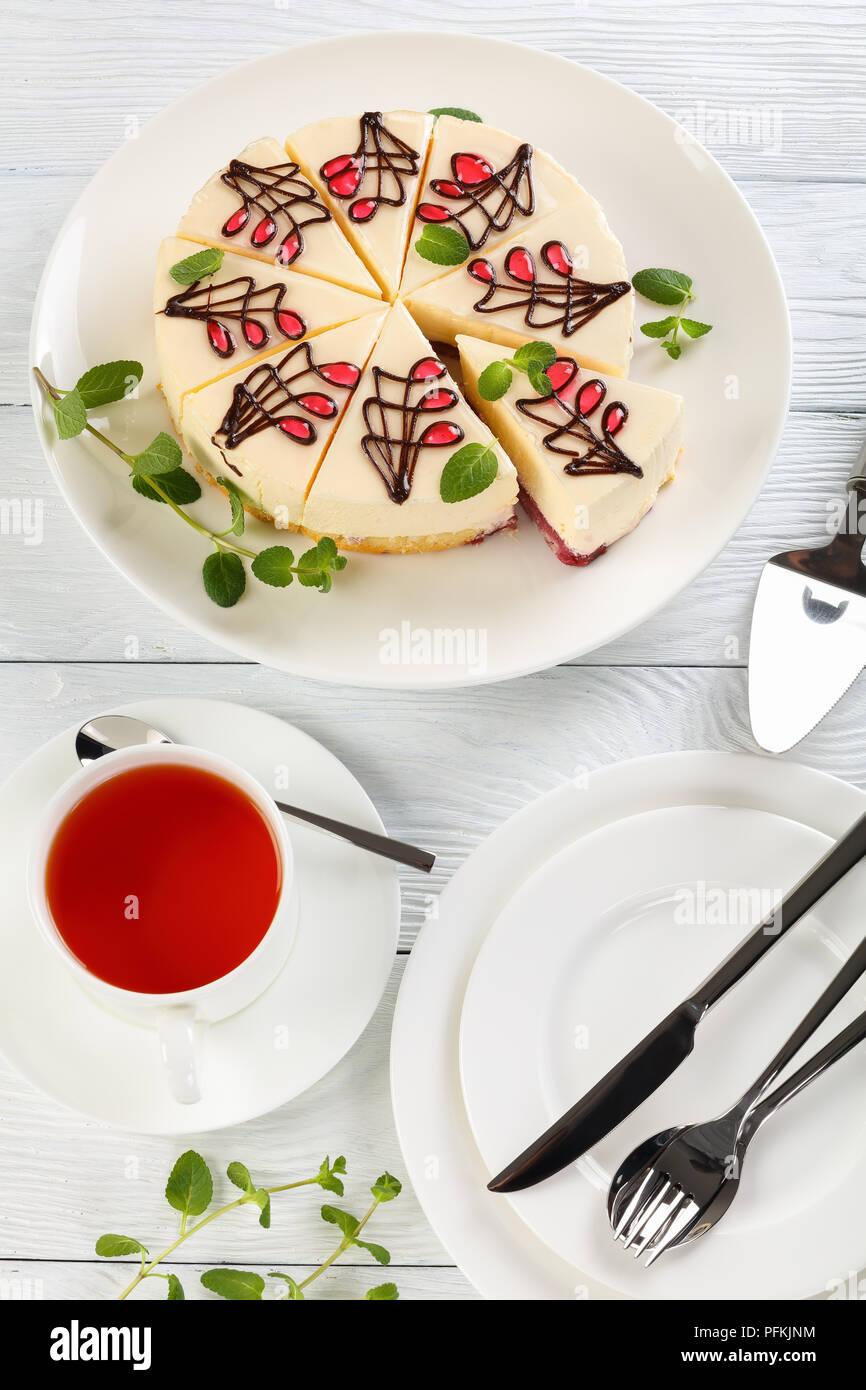 Käsekuchen von Schwamm Kuchen war mit süßen Beeren-Sauce und Frischkäse Schicht auf weißen platter auf Holztisch, Tasse Tee eingeweicht und Platten mit Silber Stockbild