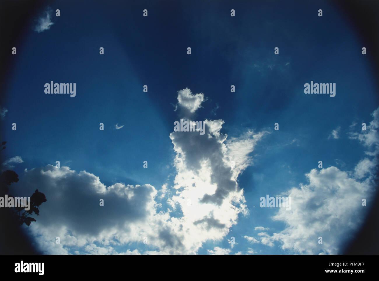 Sonnenstrahlen, fast parallel einfallender Sonneneinstrahlung teilweise durch weiße und graue Wolken, Sonne hinter zentralen Cloud beleuchten einige Teile blockiert, Strahlen cast durch blauen Himmel. Stockfoto