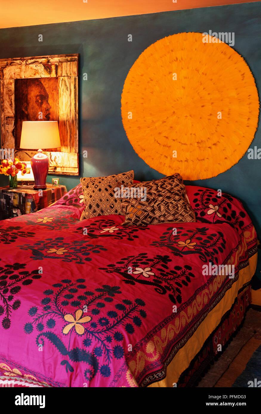 Im Indischen Stil Gestalteten Schlafzimmer Mit Rosa Und Rot Gemusterten  Bettdecken, Gold Und Braun Kissen Auf Dem Bett Verstreut, Dunkle Blaue  Wände, ...