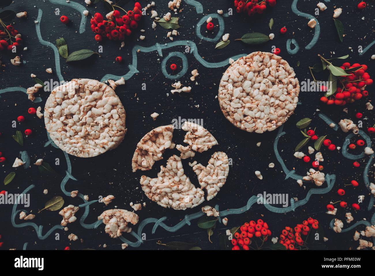 Flach knusperig Reis Kuchen auf dunklem Hintergrund mit Blumenschmuck Hintergrund, Overhead von Oben nach Unten anzeigen Stockbild