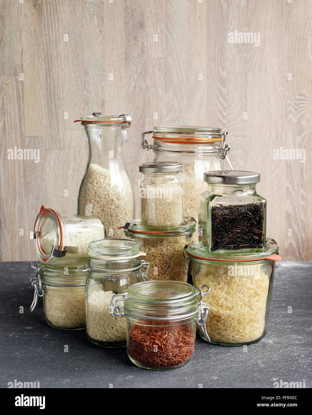 Gläser mit verschiedenen Arten von Reis, Risotto Reis, Basmatireis, Sushi Reis, klebrigen Reis, brauner Reis, Wildreis, Jasmin Reis, Pudding Reis, roter Reis (camargue Reis), langkörniger Reis Stockbild