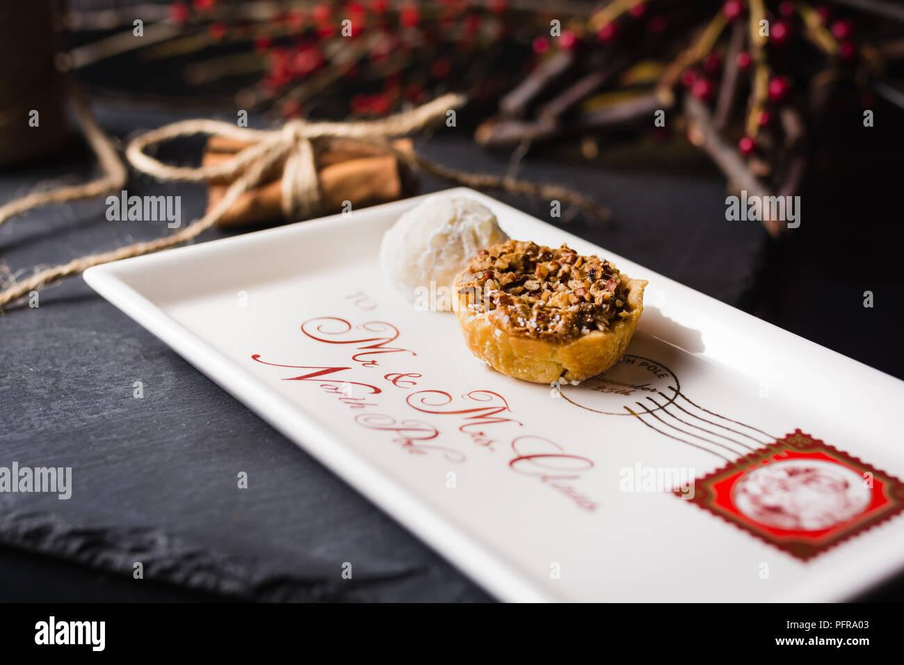 Santa Hinweis Platte mit Cookies und auf den Porto Schiefer in einem Zimt Holly Berry Hintergrund Stockbild