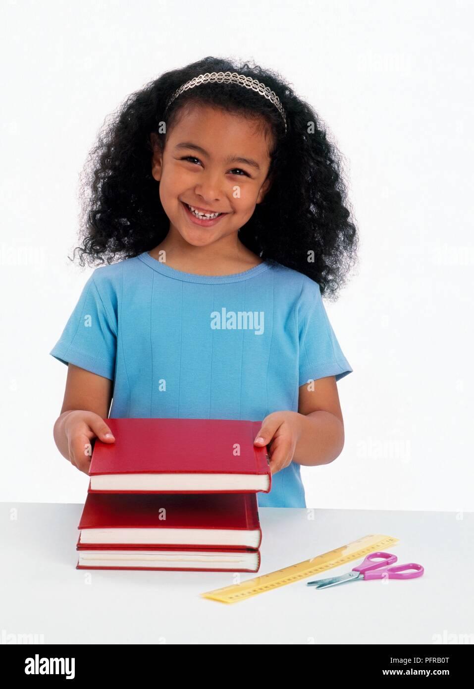 Sechs Jahre altes Mädchen hält ein rotes Hardcover Buch über zwei ...