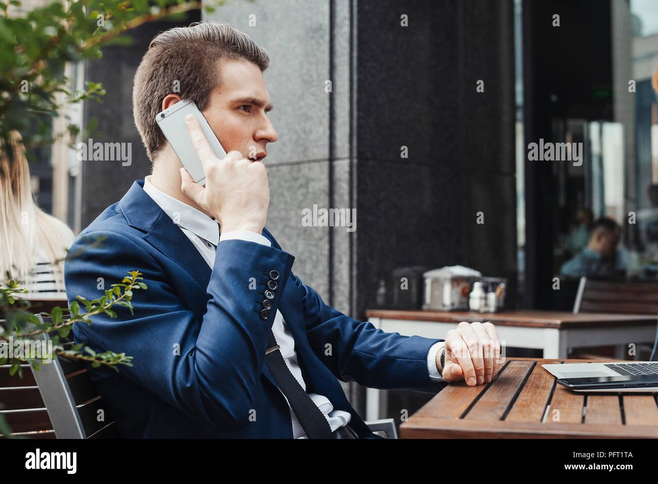 Junge attraktive Brünette Geschäftsmann Gespräch per Handy in ein Cafe. Stockbild