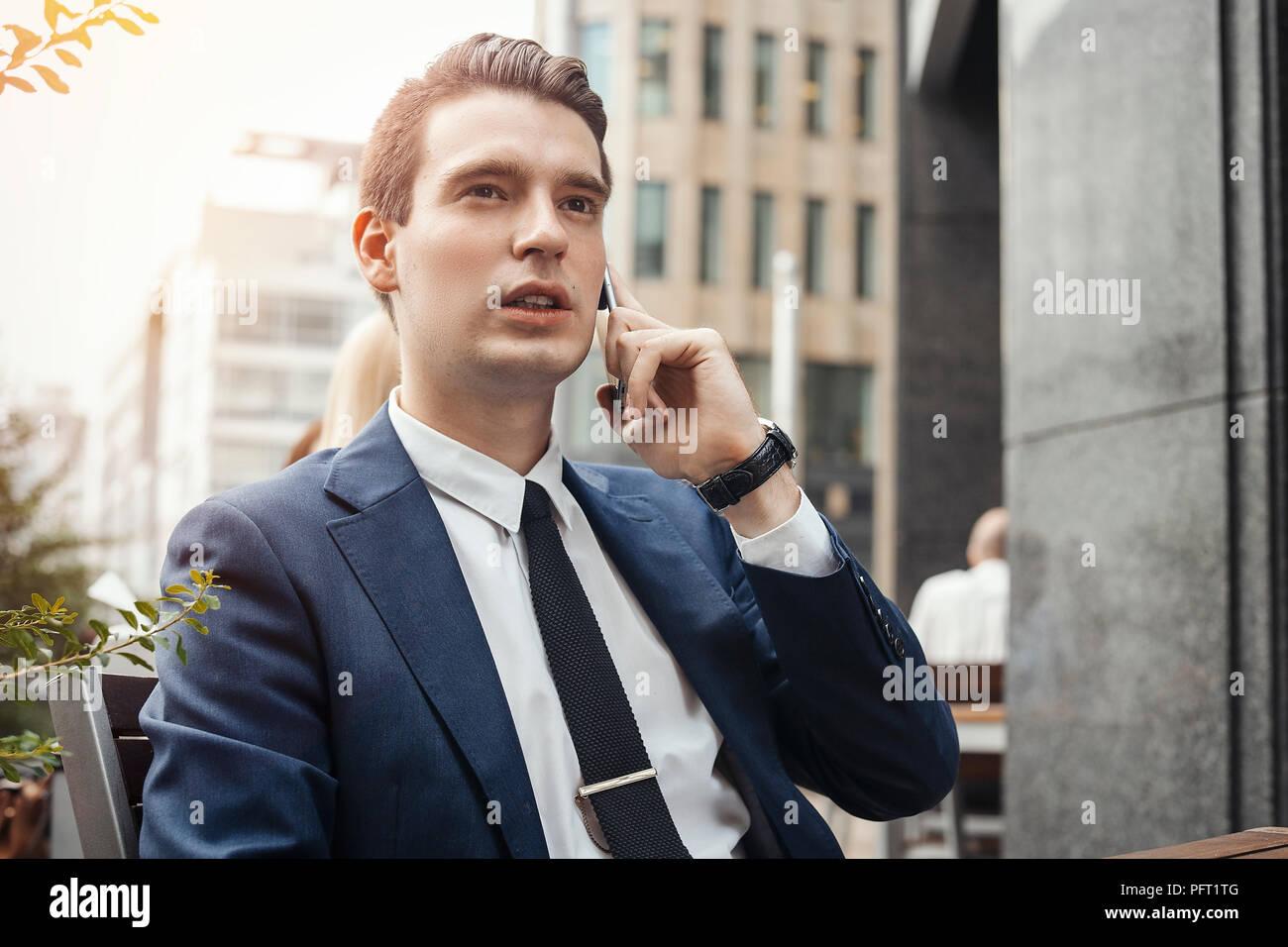 Junge brunette Geschäftsmann Gespräch per Handy und gerade auf der Suche. Stockbild
