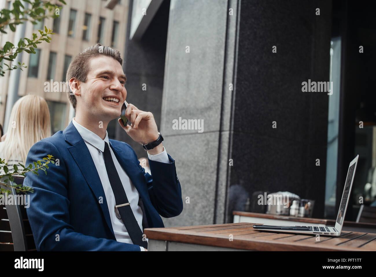 Junge attraktive Brünette Geschäftsmann Gespräch per Handy und lächelnd. Stockbild