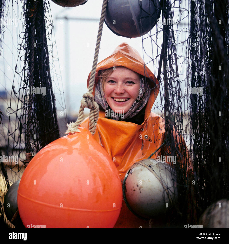 Regen in den 1960er Jahren. Eine junge lächelnde Frau ist in der regen Kleidung und Posen auf dem Deck eines Fischereifahrzeugs mit Fischnetzen. Schweden 1969 Stockbild