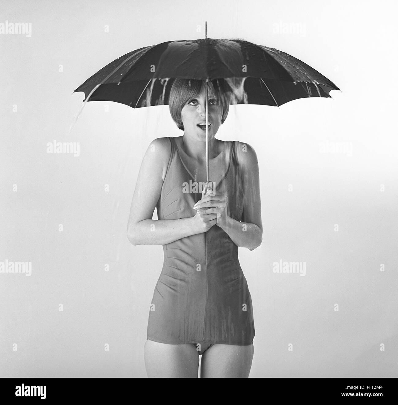 1960 s Frau. Eine junge Frau in einem Badeanzug steht unter einem Schirm. Schweden 1960 s ref TUN 42-3 Stockbild