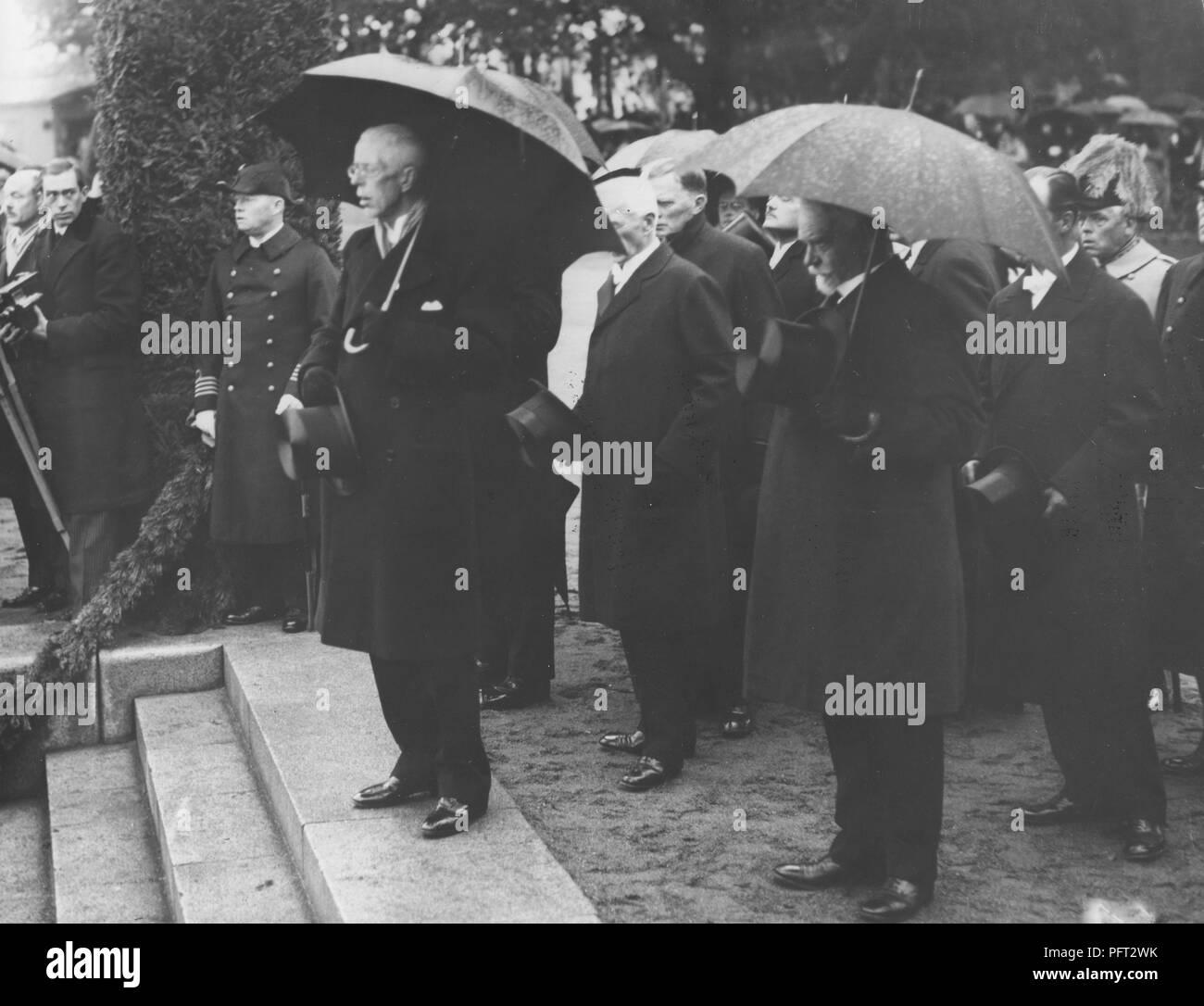 König Gustav V. von Schweden. Hier im Bild im Regen unter einem Sonnenschirm im Hafen von Stockholm warten auf das Schiff M/S Svensksund mit den Überresten von Andrée Ballon Expedition von 1897 zu kommen. Die Einrichtungen der Mitglieder wurden viele Jahre später 1930 auf der Insel Kvitøya auf Svalbard eingefroren gefunden. 1930 Stockbild