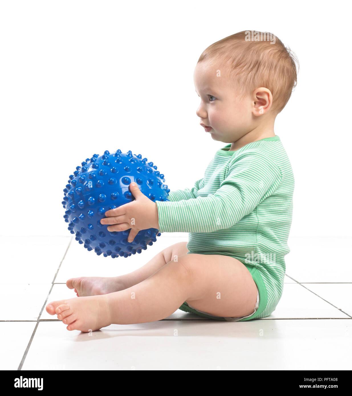 Baby Boy (12,5 Monate) sitzen hält eine holprige Ball Spielzeug Stockbild