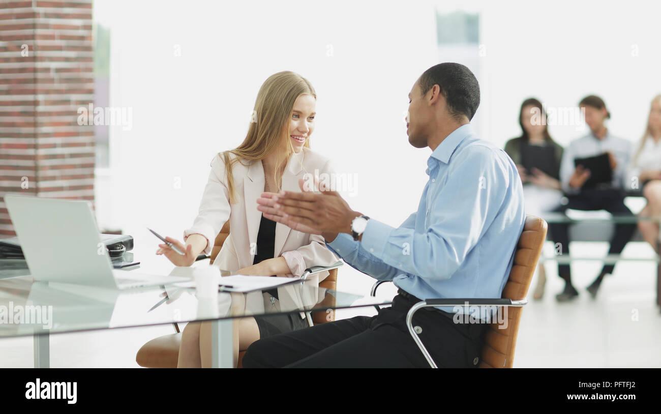 Junge Kollegen reden hinter einem Schreibtisch Stockbild