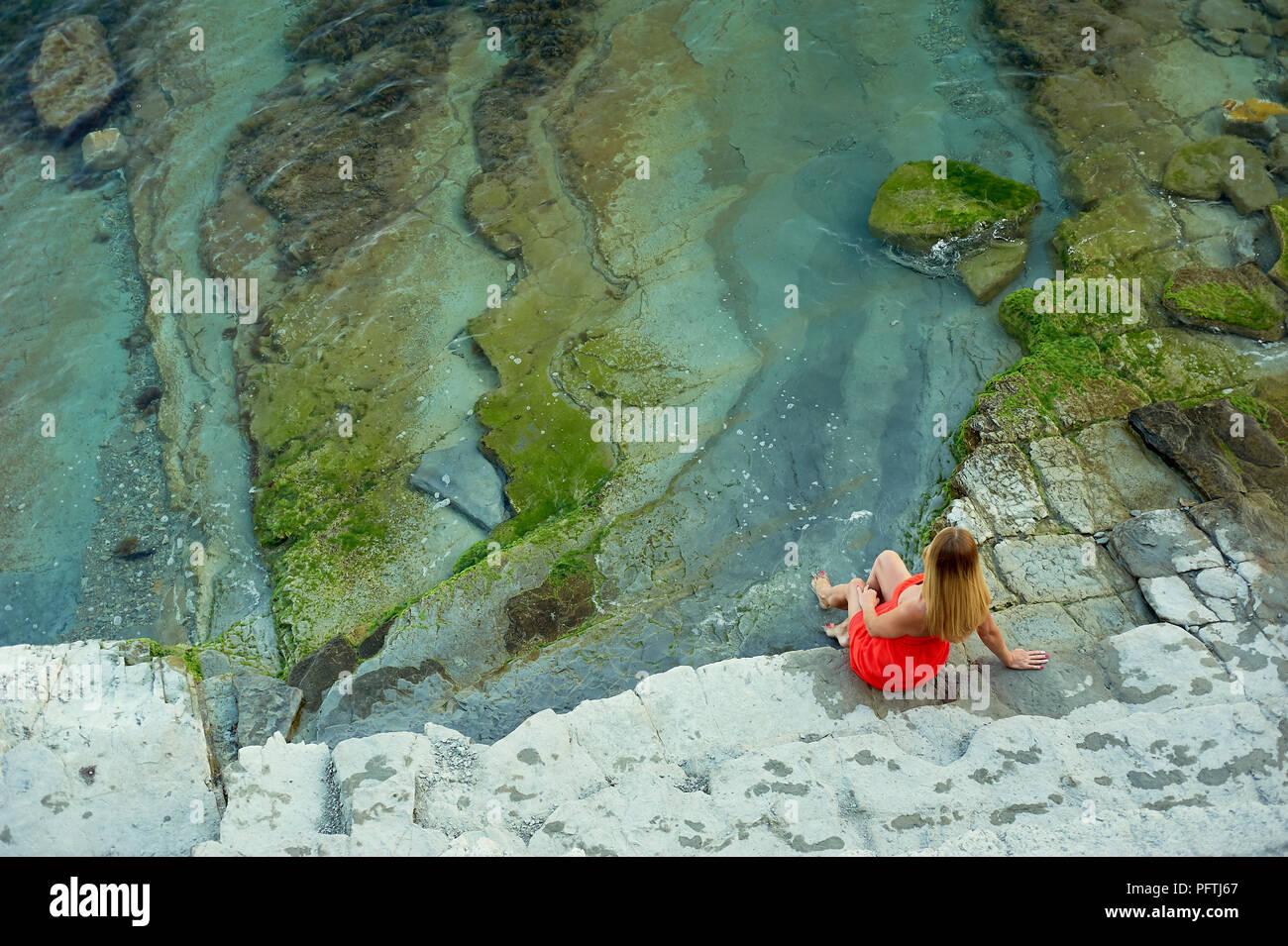 Ein Mädchen sitzt an der Klippe und blickt auf das Meer. Gefühl frei und Infinity Stockbild