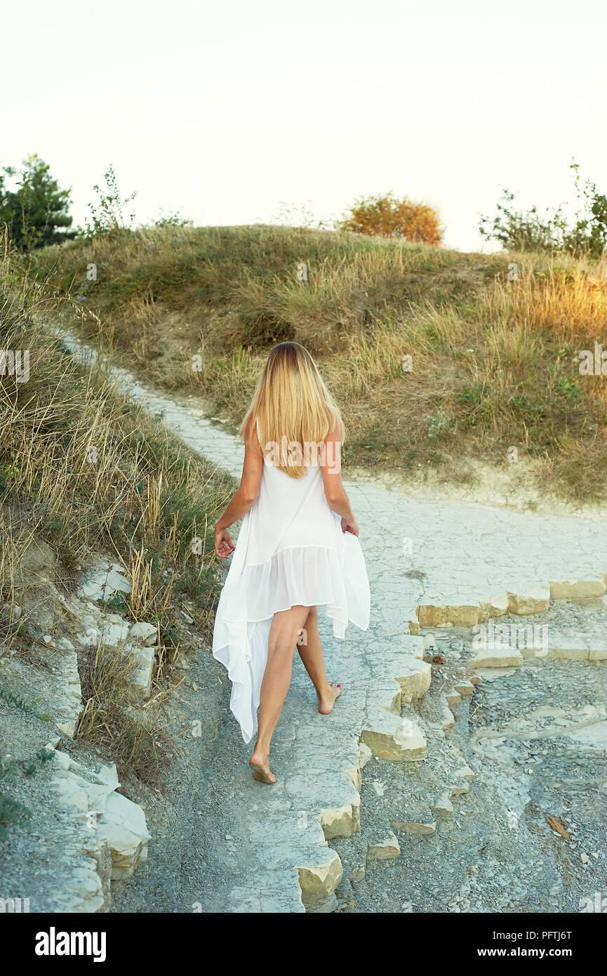 Mädchen geht auf Wüste Küsten weg, mit getrocknetem Gras. Blondine in einer weißen Tunika. Das Thema der Wüste und Meer Stockbild