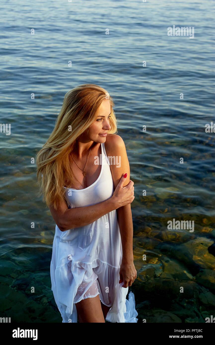 Schöne blonde Mädchen stehen Knietief im Wasser. Eine weiße Tunika. Stockfoto
