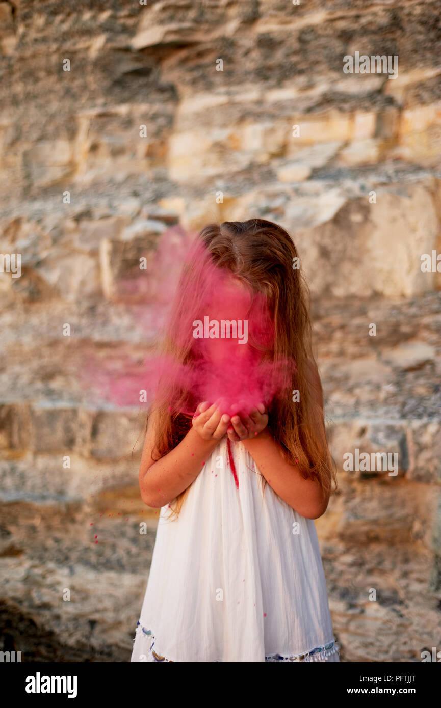 Ein kleines Mädchen mit Palmen das Blasen auf den Lack Holi rosa. Großer Moment. Stockbild