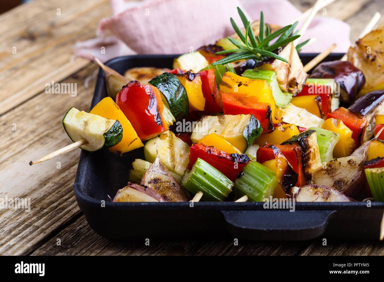 Gegrillte bunte Gemüse Spieße auf Gusseisen Skillet. Vegan Sommer Mahlzeit auf rustikalen Holztisch Stockbild