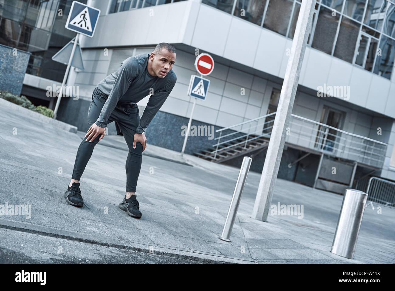 Urbane Sportarten. Junger Mann tut aufwärmen, bevor Sie in der Stadt, die auf einem Morgen Stockbild