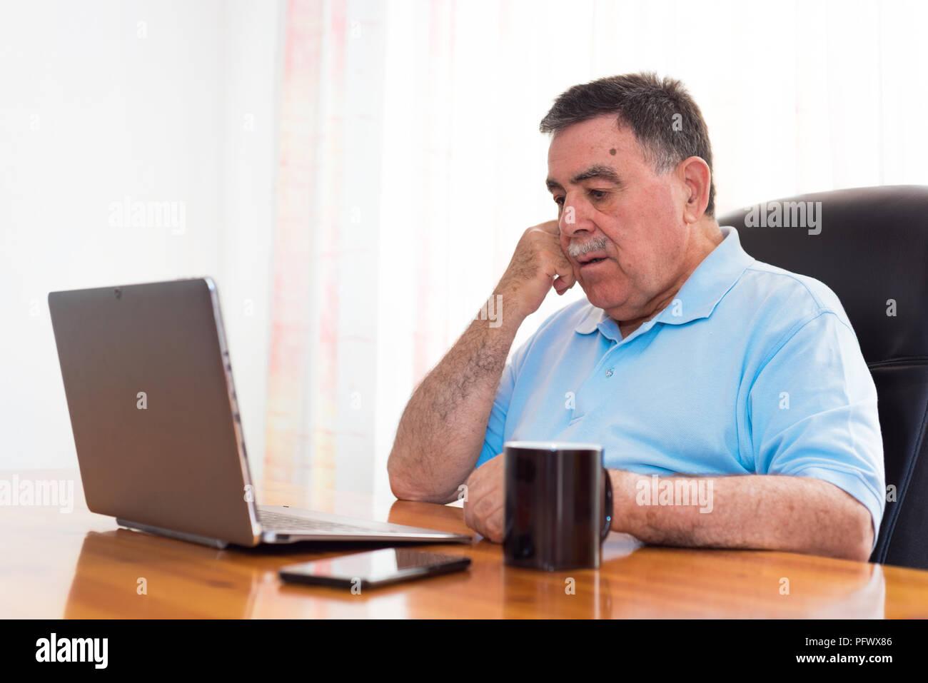 Älterer Mann mit Laptop , Ausdruck. E-Learning - Konzept. Stockbild