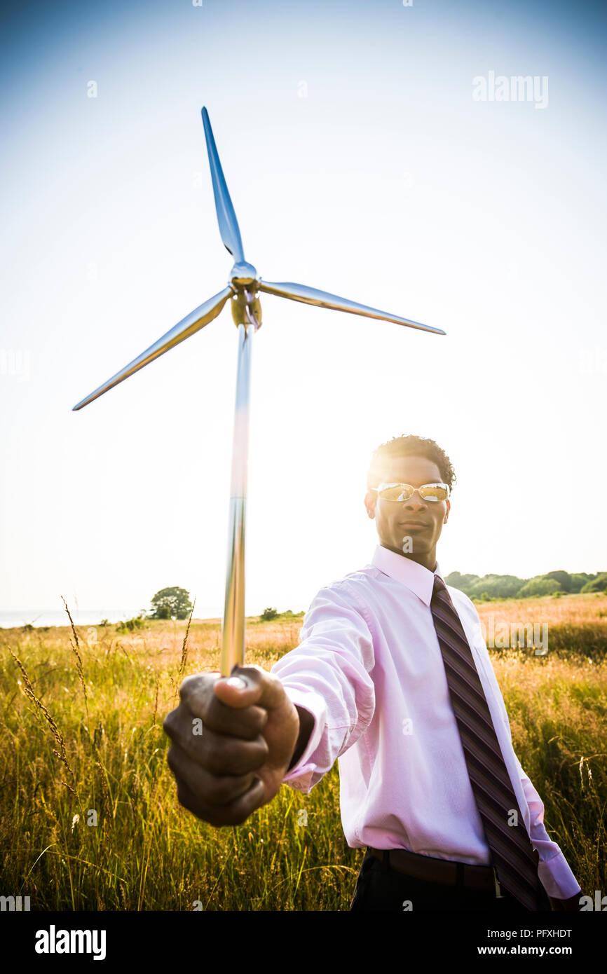 Ein afrikanischer amerikanischer Mann hält ein kleines Modell einer Windenergieanlage. Konzept der Green Energy/Green Business Stockbild