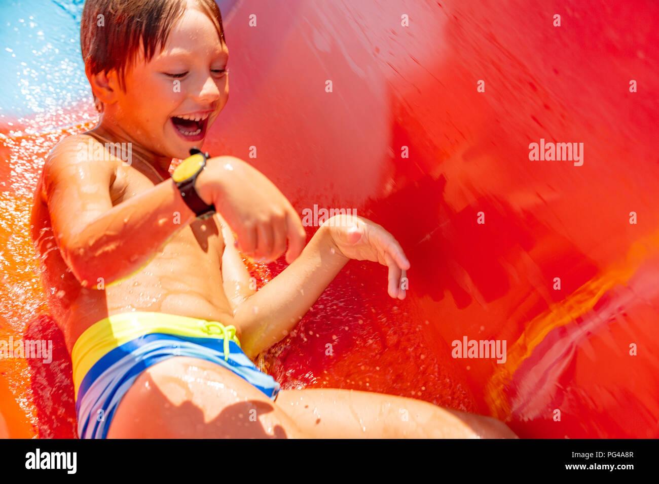 Eine glückliche junge auf Wasserrutsche in einem Schwimmbad Spaß im Sommer Urlaub in einer schönen Aqua Park. Ein Junge nach unten kriechend auf der Wasserrutsche und spritzt. Stockbild