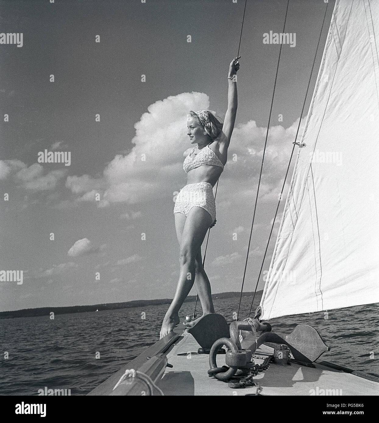 1940 s Segelboot. Eine junge Frau ist an Bord eine modische Segelboot und steht auf Deck, wenn es vorwärts Kreuzfahrten mit Wind in den Segeln. Sie trägt eine typische 40er Jahre Zweiteiliger Badeanzug. Schweden 1946 Foto Kristoffersson ref AC 101-4 Stockbild