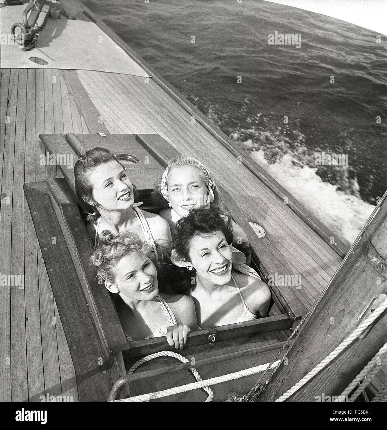 1940 s Segelboot. Vier junge Frauen sind, genießen Sie einen Tag am Meer auf einem eleganten hölzernen Segelboot. Sie haben unter Deck gewesen und jetzt werden Sie durch die Klappe und lächelt. Schweden 1946 Foto Kristoffersson ref AC 101-5 Stockbild