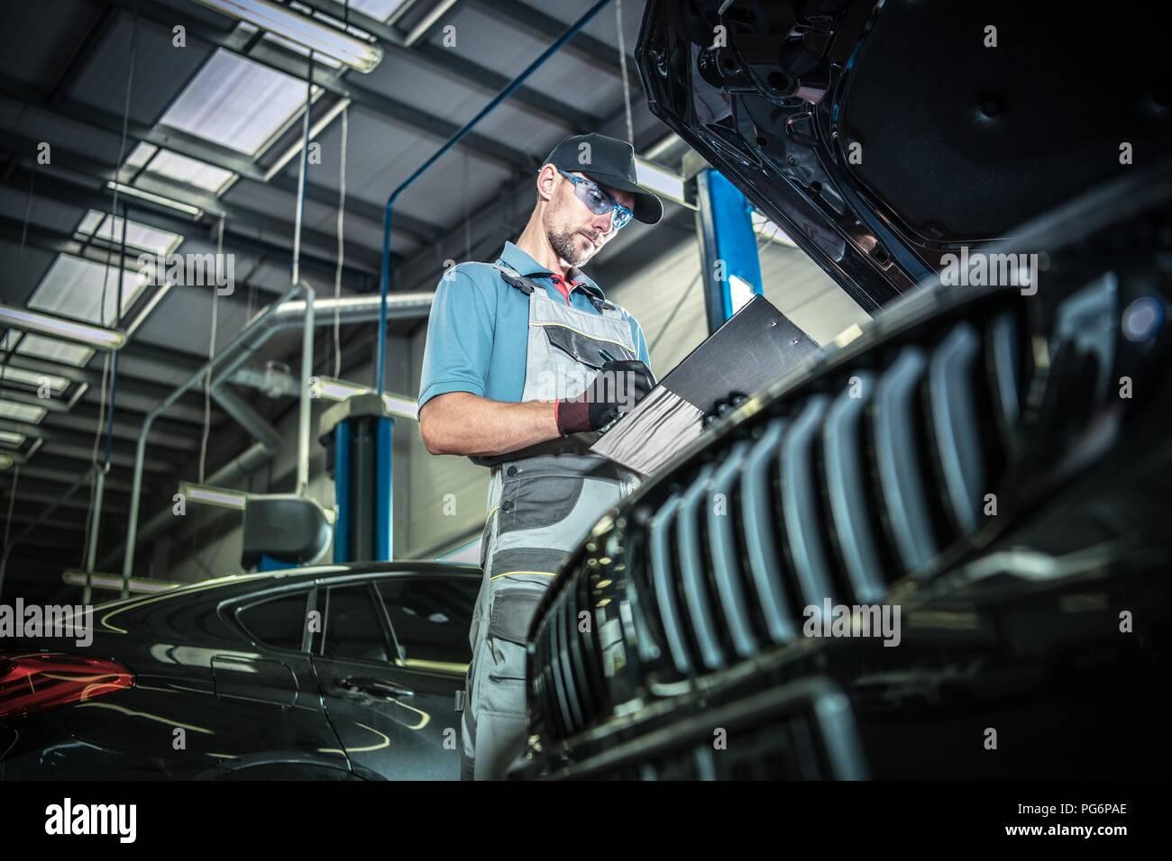 Kaukasische Automechaniker in seinem 30s Durchführung der Wartung des Fahrzeugs mit einer Dokumentation in der Hand. Stockbild