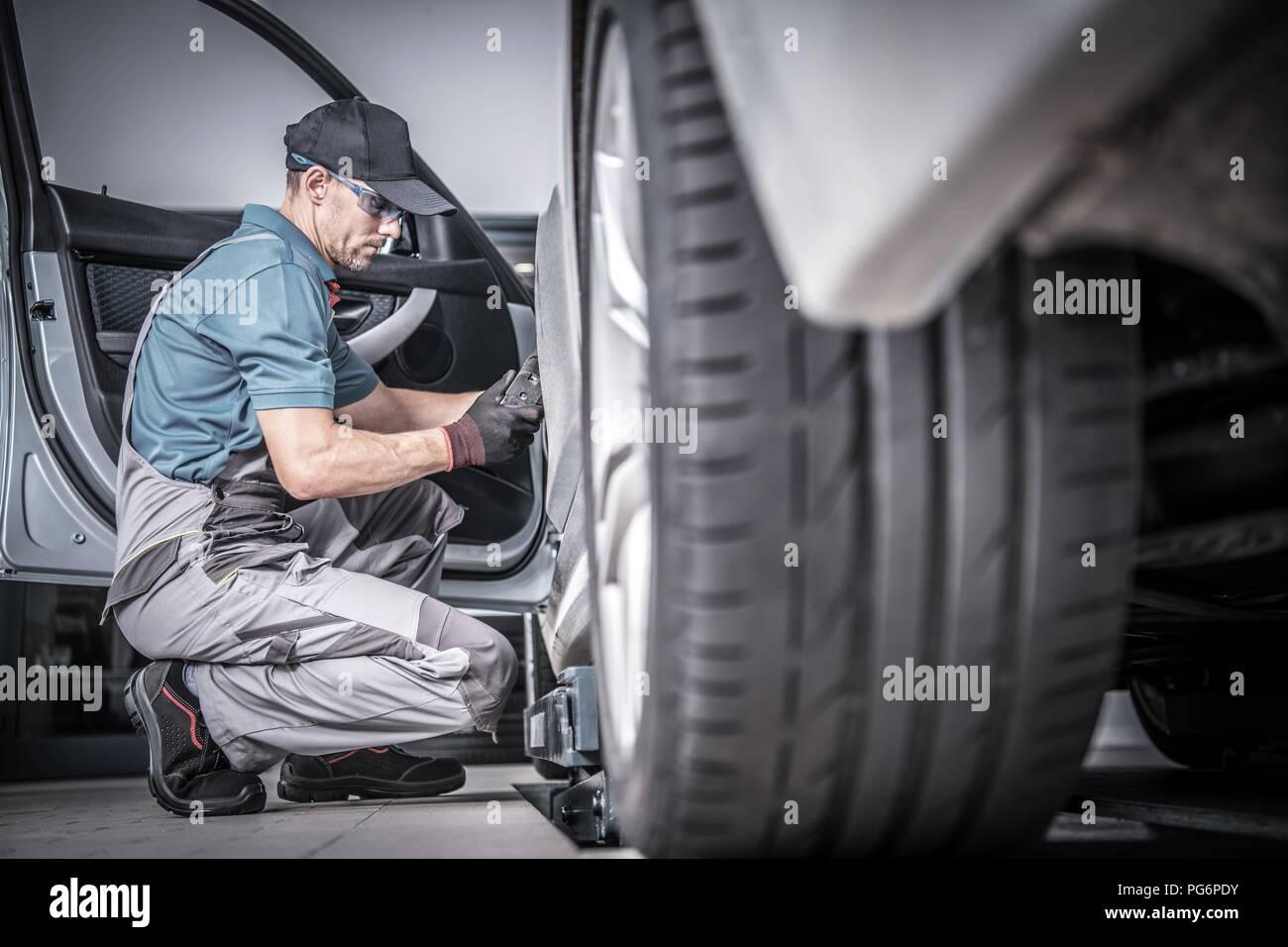 Auto unter Instandhaltung verwendet. Kaukasische Automechaniker auf der Suche nach möglichen Problemen im Fahrzeug. Stockbild