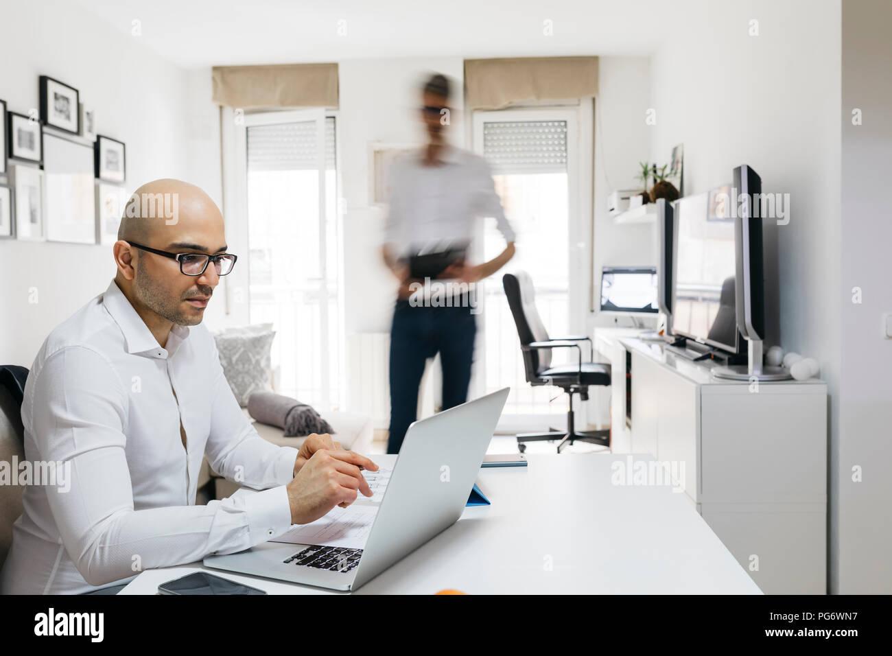 Mann mit Laptop im Home Office mit Kollege bewegte Vergangenheit Stockbild