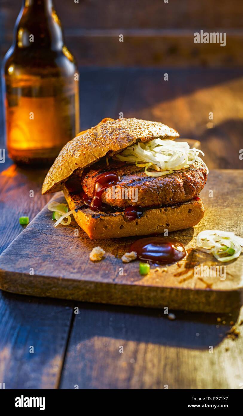 Burger auf Holzbrett neben Bier Flasche Stockbild