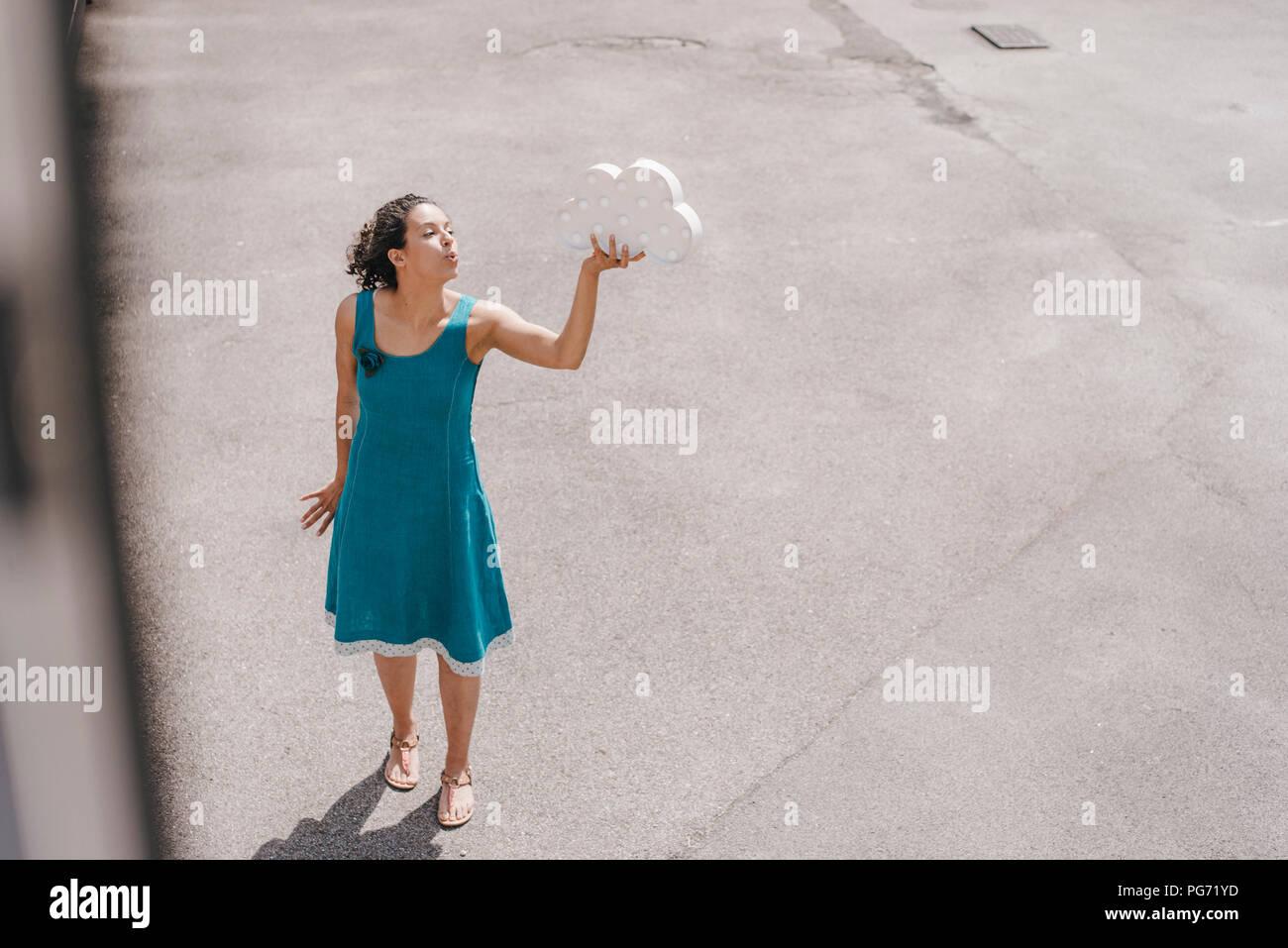 Frau, die in den Hinterhof, Holding cloud Symbol, Blasen küssen Stockfoto