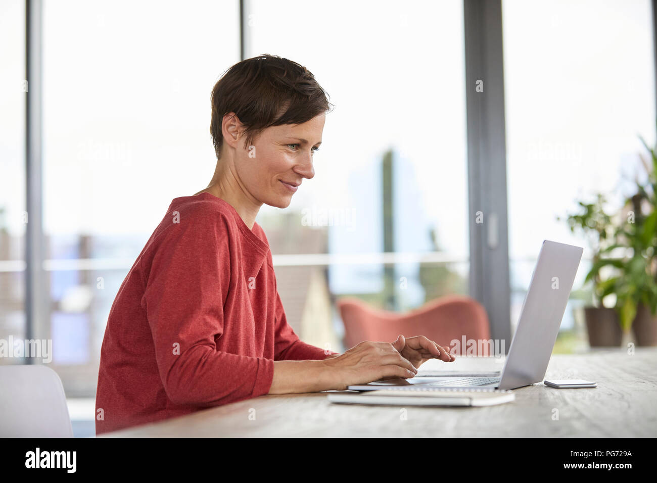 Lächelnde Frau am Tisch zu Hause sitzt mit Laptop Stockbild