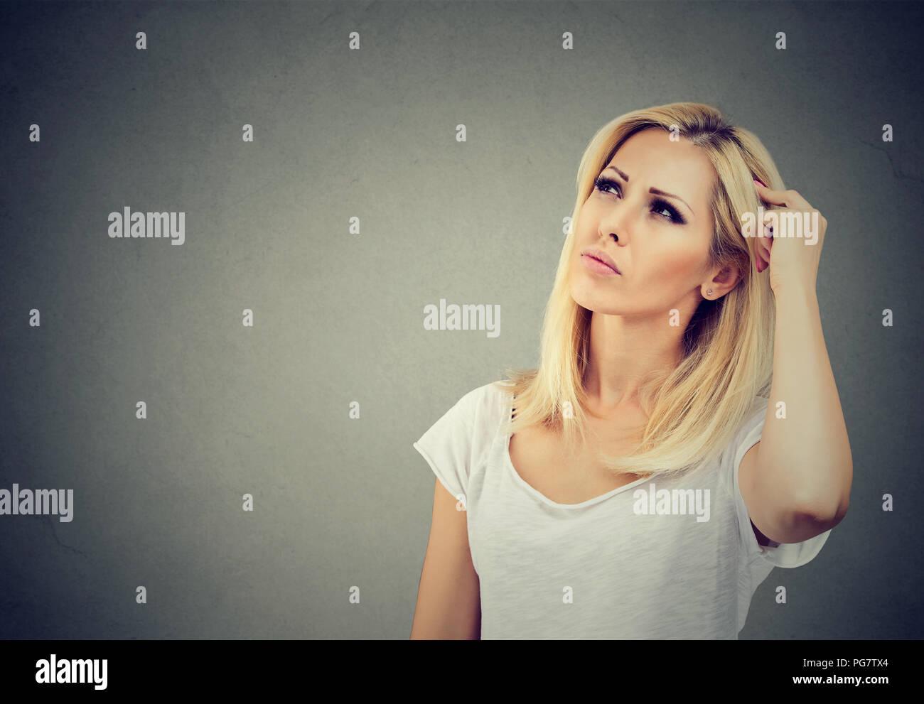 Junge nachdenkliche Frau suchen in Achtsamkeit in Memory Problem auf grauem Hintergrund Stockbild