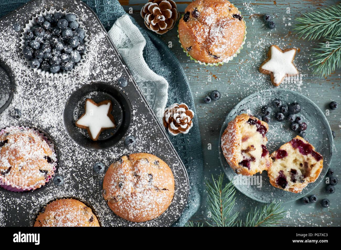 Blueberry Muffins mit Zuckerguss in einem Backblech mit Weihnachtsschmuck rund, flach, Ansicht von oben Stockbild