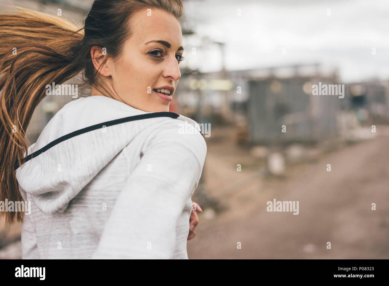 Sportliche junge Frau läuft im Freien Stockbild