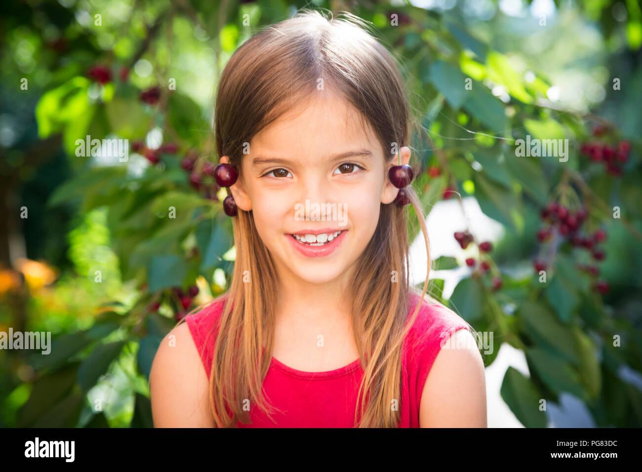 Kleines Mädchen mit Kirschen auf den Ohren Stockbild