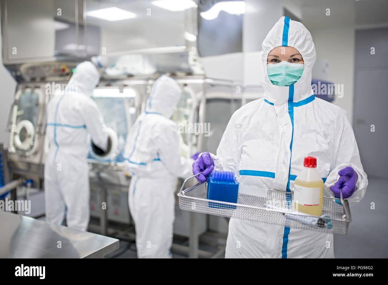 Techniker Ausrüstung, die in einem Labor, das menschliche Gewebe zur Implantation. In der Flasche ist die physiologische Lösung, die hilft, Zellen in vitro zu erhalten. Gewebe im Werk hergestellt werden Knochen und Haut. Stockbild