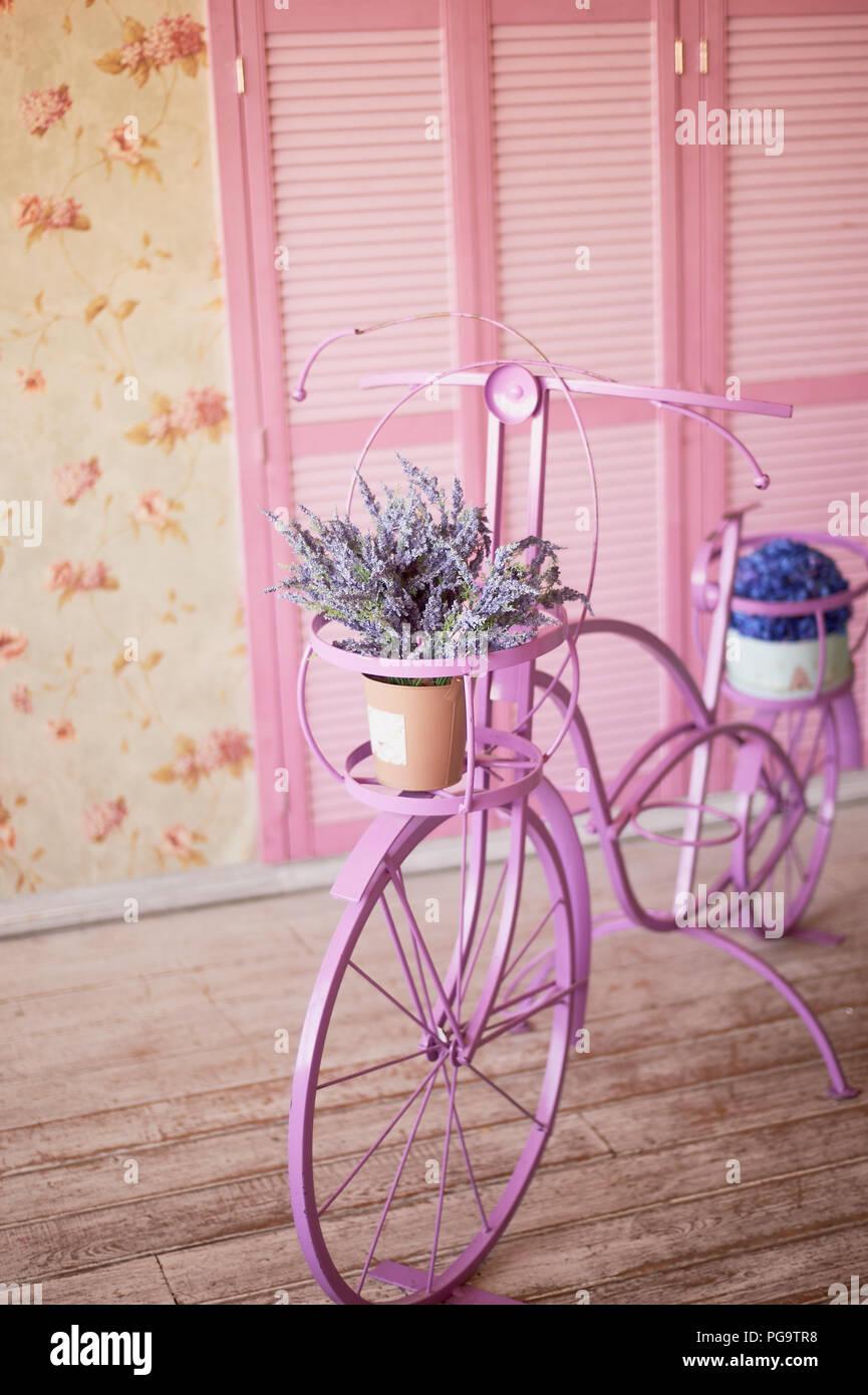Rosa dekoratives Fahrrad auf rosa Hintergrund. Blume Wallpaper Stockfoto