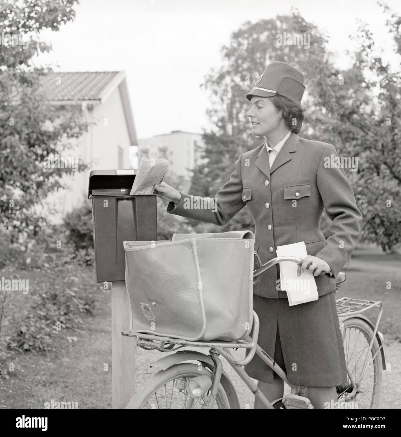 1960 Briefträger. Eine Frau in die schwedische Post einheitliche bietet e-mail, und legen Sie die Briefe in einer Mailbox. Schweden der 60er Jahre. Foto Kristoffersson GD 114-7 Stockbild