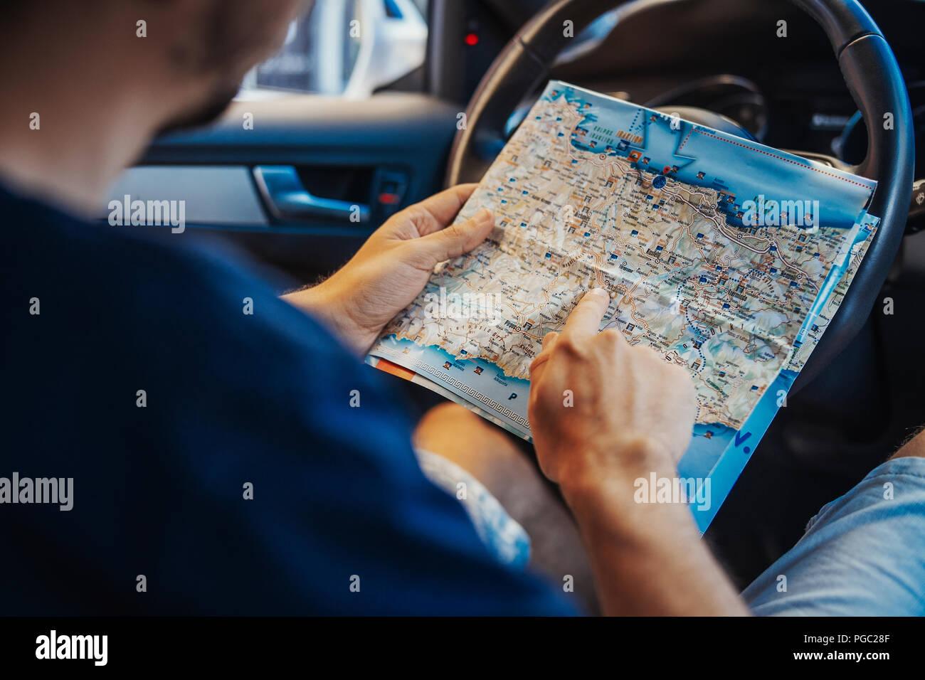 Der junge Mann an der Karte hinter dem Lenkrad im Auto suchen. Der Mensch ist der Mittelpunkt und Vordergrund, Auto ist auf Hintergrund und verschwommen. Ansicht von hinten Stockbild