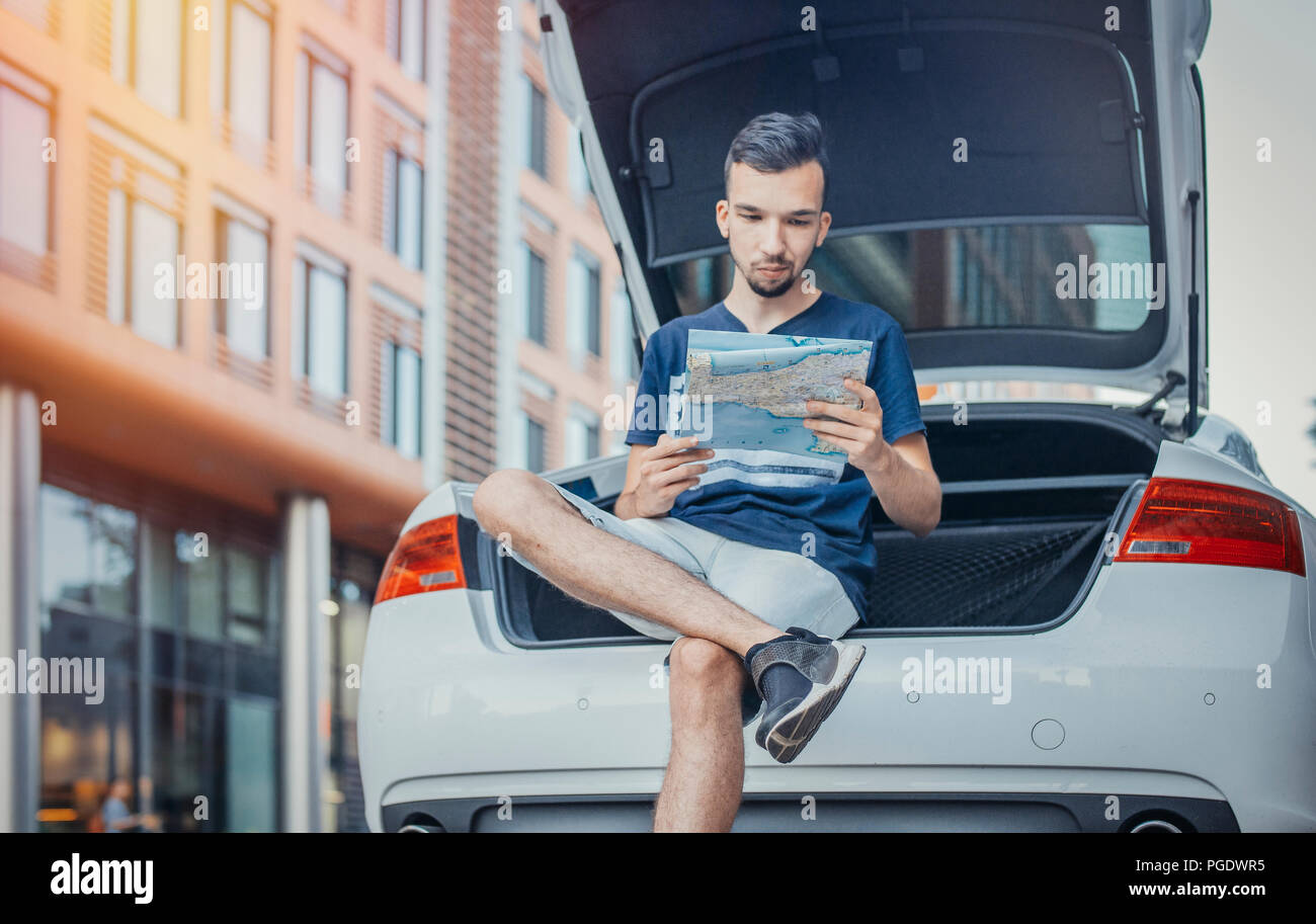 Ferner Plan der junge Mann an der Karte im Fahrzeug von Auto sitzen. Mensch und Auto sind im Mittelpunkt und Vordergrund, Hintergrund verschwommen. Ansicht von vorn Stockbild