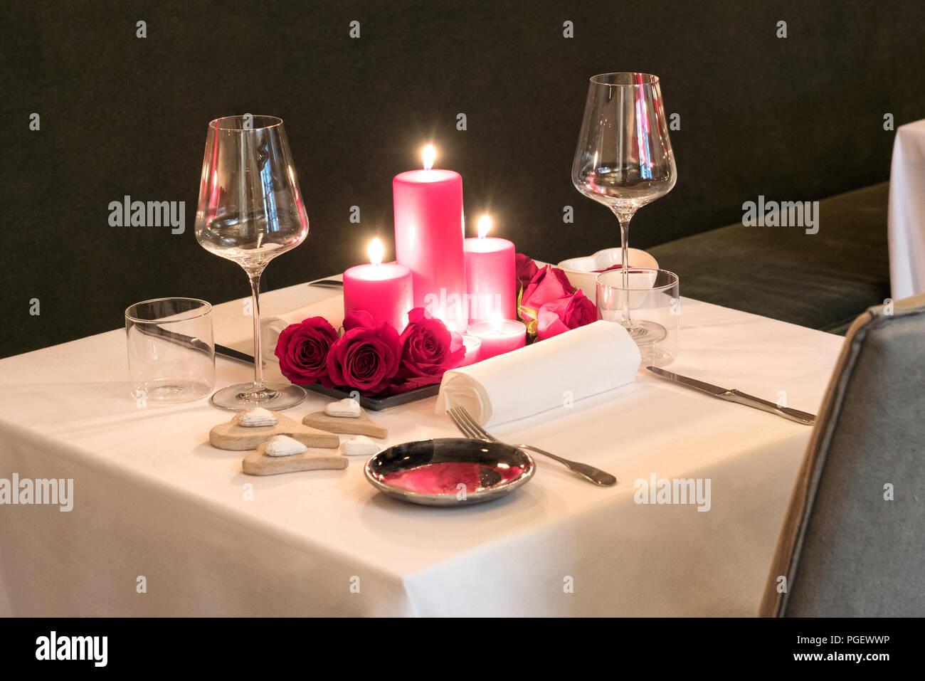 Hochwertig Romantisches Dinner Bei Kerzenlicht Gedeckten Tisch Für Zwei Mit Einem  Herzstück Der Brennende Rote Kerzen Und Frische Blumen Mit Passenden Roten  Geschirr ...