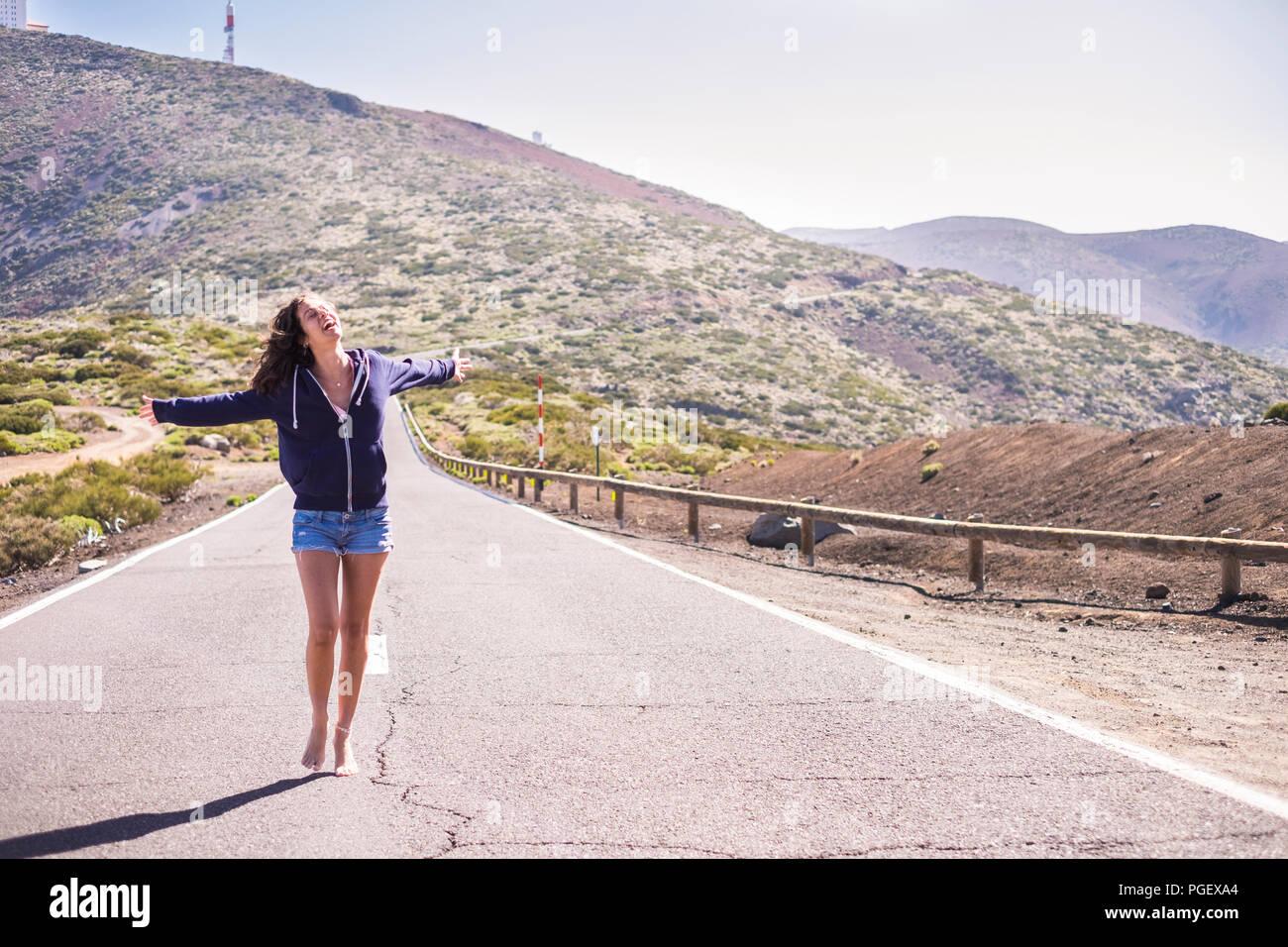 Schöne junge Frau barfuß über einen langen Weg Straße am Berge. Glück und freudige Konzept für kaukasische Modell mit schönen Beinen und Shorts. Stockbild
